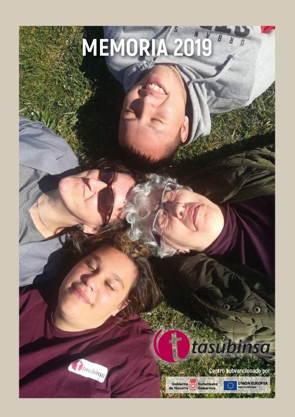 Cuatro personas de Tasubinsa, sonrientes y tumbadas en la hierba